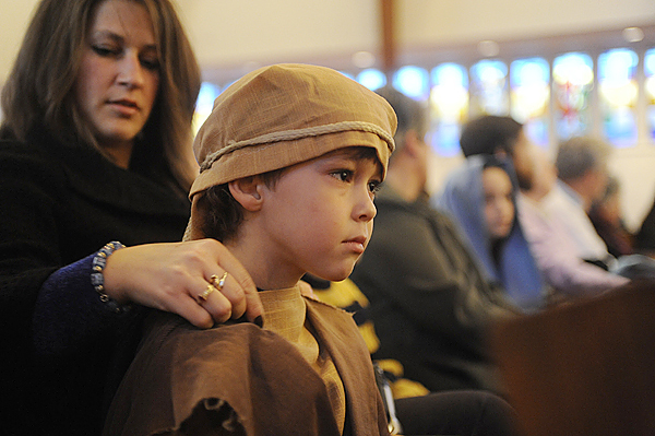 Whie seated with other parishioners, Leslie Long of Brewer adjusted the shepherd's head covering on her son, Kyle Long, 5 before he joined other children in a nativity scene during the celebration of Christmas Eve Mass at St. Joseph's Catholic Church in Brewer Thursday evening, December 24, 2009. BANGOR DAILY NEWS PHOTO BY JOHN CLARKE RUSS