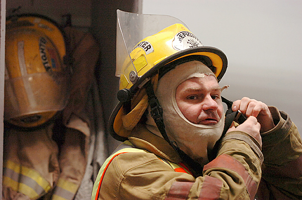 David Ledin, 44, of Plymouth tightens his helmet strap in preparation for a training session Wednesday, Dec. 16, 2009 at the Etna Volunteer Fire Department which Ledin has volunteered at for several years. &quotProbably the biggest thing Dave contributes is spirit,&quot said Fire Chief Walter Gibbons of Ledin's involvement with the department. Though Ledin is developmentally disabled, he is able to hold down a job, volunteer and is currently learning to read for the first time. Besides his enthusiasm for the fire department, Ledin has a passion for 18-wheeler trucks, cowboy paraphernalia and NASCAR. (Bangor Daily News/Bridget Brown)