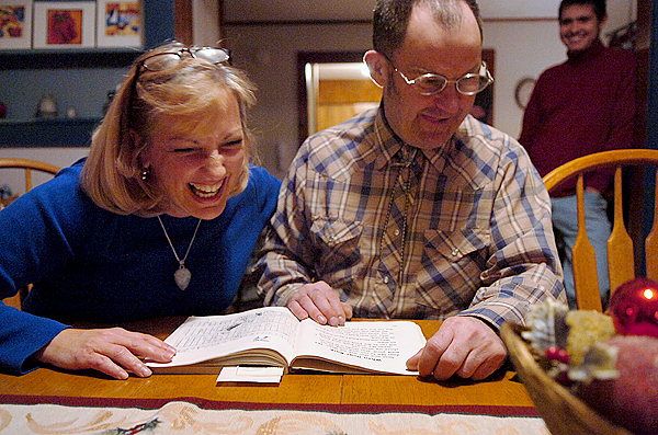 Laurie Berube Giles and David Ledin share a laugh while the two practice Ledin's reading skills Sunday, Dec. 13, 2009 at the Plymouth home they share along with Giles' husband Steve and son Jonathan. The Gilles have hosted Ledin in their home for over three years through a program with Living Innovations which aims to place developmentally disabled adults in family homes rather than group homes or other living arrangements. (Bangor Daily News/Bridget Brown)
