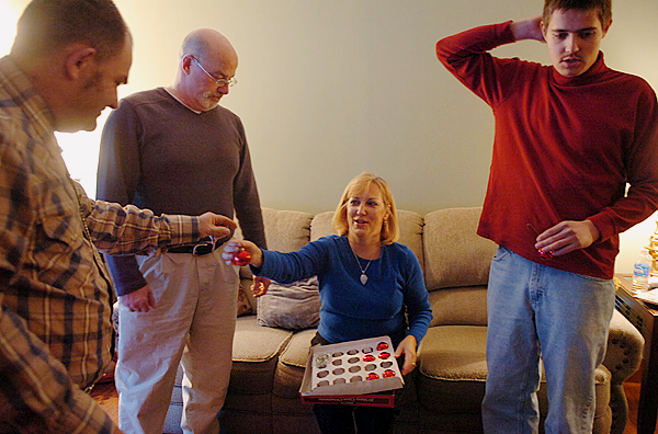 Laurie Berube Giles hands David Ledin (left) a Christmas ornament to place on the famiy's tree as her husband Steve Giles (second from left) and son Jonathan Kaufmann (right) look on Sunday, Dec. 13, 2009 at the Plymouth home the four share. The Gilles have hosted Ledin in their home for over three years through a program with Living Innovations which places developmentally disabled adults in family homes rather than group homes or other living arrangements. (Bangor Daily News/Bridget Brown)