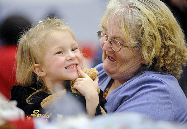 Clutching her stuffed toy bear, three-year-old Ashley Smith of Brewer beams a smile to other family members while sitting in the lap of her great-grandmother Caroline Laird of Bangor during Manna's Christmas dinner at Bangor Parks and Rec  Friday, December 25,2009. (Bangor Daily News/John Clarke Russ)