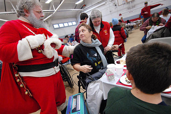 Santa, left, prays with Julie Dominguez (seated) of Carmel, her son Austin Slover, 13 of Carmel and volunteer Ella Weeks of Exeter (standing with head bowed) during Manna's Christmas dinner at Bangor Parks and Rec Center Friday, December 25,2009. Dominguez who took part in the Christmas celebration, said she is on the mend from a recent ATV accident near her home and asked Santa to pray with her for her recovery. (Bangor Daily News/John Clarke Russ)