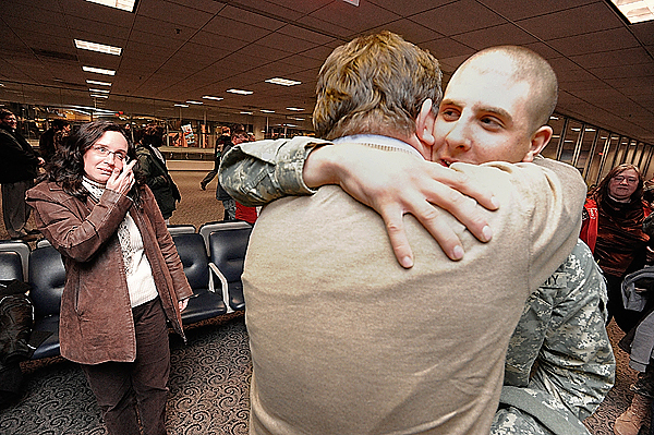 Private First Class Zane Clossey,19, hugs his dad, Harold Clossey of Robbinston after his civilian flight arrived at Bangor International Airport early Saturday morning, December 19, 2009. On the left is his mom, Trish Hopkins, of St. Stephen, New Brunswick. The young Clossey just finished basic training and heads to Fort Hood after visiting his family on both sides of the border over the holidays. BANGOR DAILY NEWS PHOTO BY JOHN CLARKE RUSS