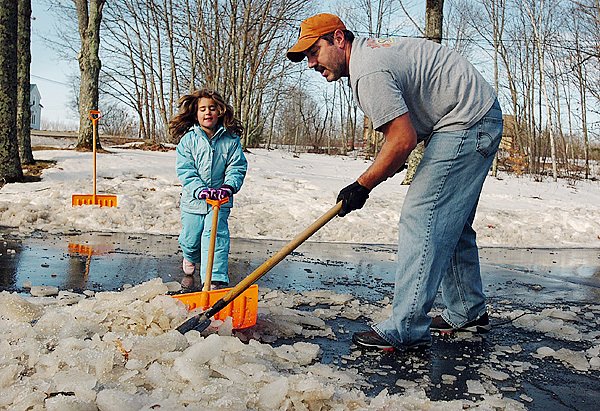 Norm Veillette, right, and his daughter, Olivia, left, of Glenburn, scrape and shovel ice from the driveway of their home on Ohio Street on Monday, December 28, 2009. (Bangor Daily News/Kevin Bennett)