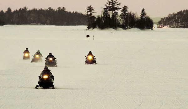 Snowmobilers head across Moosehead Lake near Greenville at dusk last week. The state has recorded 14 snowmobile deaths this winter, and the season is not over. Some areas have enough snow to accommodate a couple more weeks of sledding.   AP PHOTO BY PAT WELLENBACH