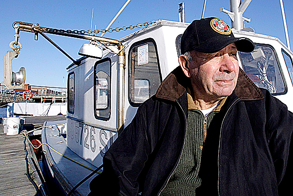 In this photo taken  Dec. 17, 2009, fisherman Joe Sava, 75, poses on his fishing boat &quotLittle Hunter&quot in Gloucester Harbor in Gloucester, Mass.  AP PHOTO BY CHARLES KRUPA