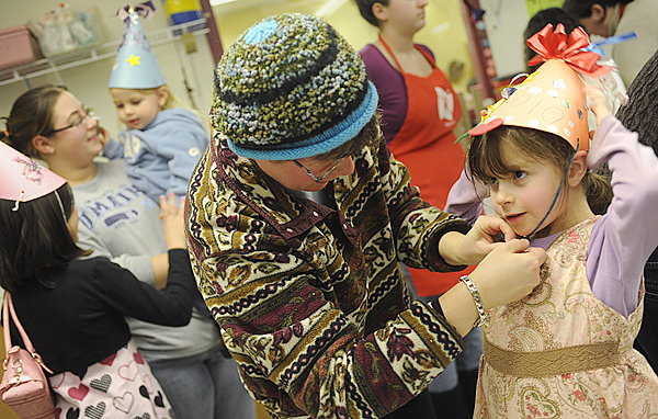 Maayan Freedberg (cq), 6 of Bangor gets help from her mom, Naomi Freedberg, as they strap on her self-crafted New Years party hat during Thursday afternoon's noisemaker and hat making party at Maine Discovery Museum. Behind them are Mikayla Smith (lower left) 9, of Brewer and Danielle Rideout holding her two-year-old daughter Lily Rideout. New Years events took place across the region to usher in 2010. BANGOR DAILY NEWS PHOTO BY JOHN CLARKE RUSS