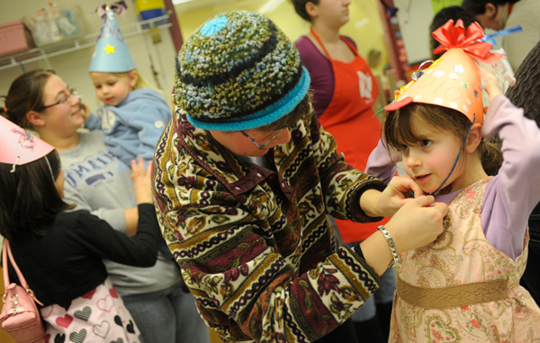 Maayan Freedberg (cq), 6 of Bangor gets help from her mom, Naomi Freedberg, as they strap on her self-crafted New Years party hat during Thursday afternoon's noisemaker and hat making party at Maine Discovery Museum. Behind them are Mikayla Smith (lower left) 9, of Brewer and Danielle Rideout holding her two-year-old daughter Lily Rideout. New Years events took place across the region to usher in 2010. (Bangor Daily News/John Clarke Russ)