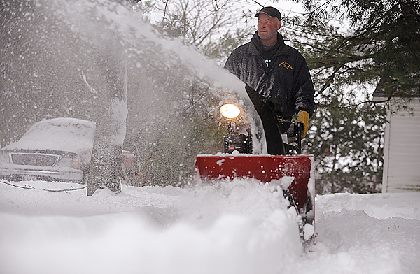 Jim Runnells uses his snowblower to remove the white stuff from his dooryard off outer Essex Street in Bangor Sunday morning following the overnight snowfall. &quot I don't mind [the snow],&quot said Runnells. &quotI work outdoors. I deliver propane.&quot (Bangor Daily News/John Clarke Russ)