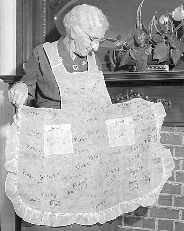 Mrs. Mary Neal, 81, of Sherman Mills, who is visiting her daughter, Mrs. Kenneth Springer of 145 Elm Street, Bangor, has an unusual apron of white organdy which was made by another daughter, Mrs. Jerry O'Roak of Sherman Mills. Embroidered on the apron are the names of Mrs. Neal's 112 grandchildren and great-grandchildren.  BANGOR DAILY NEWS FILE PHOTO BY CARROLL HALL