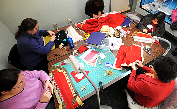 A group of women including Wabanaki textile artists work on a replica of a 1700's Maliseet chief's coat ensemble at the Maine State Museum in Augusta. When the ensemble is complete it will be part of the museum's permanent collection in the Uncommon Threads exhibit. The original - owned by a museum in Canada - is so fragile that it can not be exhibited.  Pictured are from lower left: from left, Frances Frey, Laurie LaBar, Marion Scharoun, Jennifer Neptune (top right) and Rose Tomah (bottom right).  (Bangor Daily News/Gabor Degre)