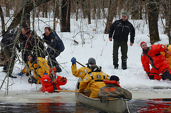Maine State Police and wardens from the Dept. of Inland Fish and Wildlife, along with the Milford and Old Town water rescue team land a canoe containing rescue personnel and power tools on Olaman Island on Monday, Jan. 4, 2009. Hovercraft and air boats couldn't navigate the narrow rivers of water as crews worked to reach a plane crash on the small island. BANGOR DAILY NEWS PHOTO BY KEVIN BENNETT