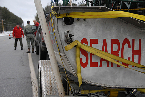 A Maine Warden Service search and rescue boat on a trailer waits in reserve on Route 2 in Olamon as public safety officials reached the downed Cessna which crashed on Olamon Island Monday morning, Janaury 4, 2010. BANGOR DAILY NEWS PHOTO BY JOHN CLARKE RUSS