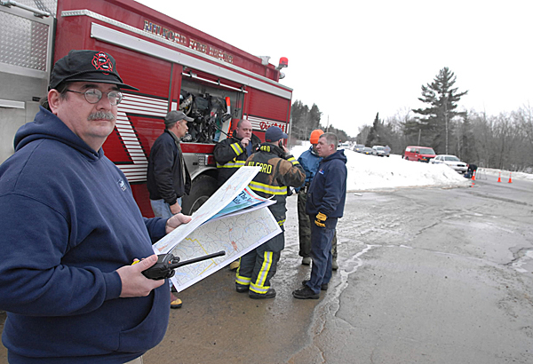 Local firefighters and others gathered at a staging area at the intersection of Military Road and the Main Road (Rt. 2) in Greenbush as fellow public safety officials reached the downed Cessna which crashed on Olamon Island Monday morning, Janaury 4, 2010. BANGOR DAILY NEWS PHOTO BY JOHN CLARKE RUSS