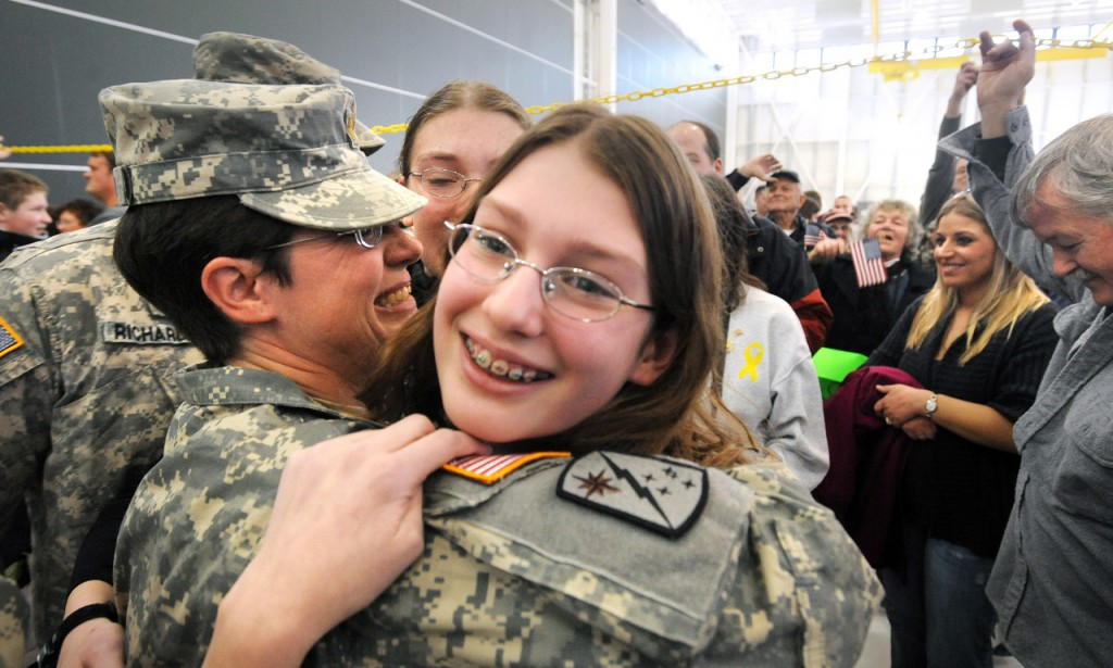 Maj. Lydia Jordan, 42, of Bowdoin (left) is greated by her daughters Abby, 12, (center) and Elsie, 14, (obscured) during the Homecoming Ceremony of the Maine Army National Guard 286th Combat Sustainment Support Batallion in Bangor Wednesday.  Jordan was one of 81 soldiers who returned from a year long deployment to Afghanistan. (Bangor Daily News/Gabor Degre)