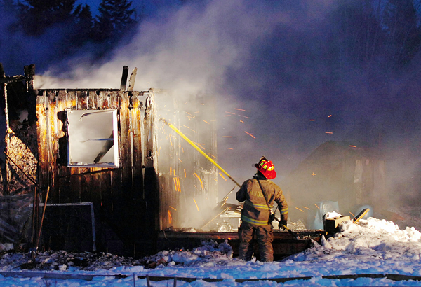 Lt. Josh Lilley of the Hudson Fire Department picks apart the remains of a Glenburn home on the Hudson Road that was destroyed in a fire Thursday evening. According to Capt. Gene Hamm of the Glenburn Fire Department, the house was fully involved upon arrival and no one was injured in the blaze. Buy Photo