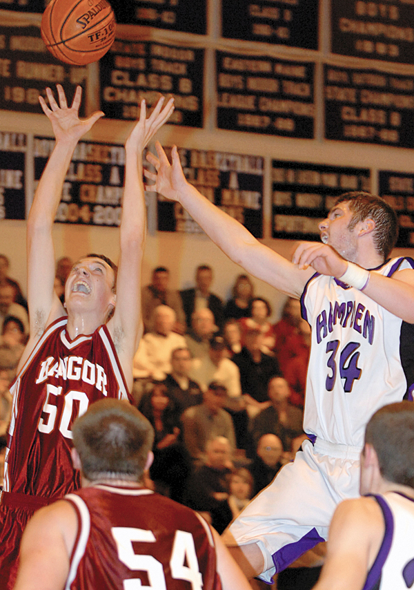 Bangor's Patrick Stewart (left) snatches the rebound ahead of Hampden's Noah Burditt in the first half of Thursday's game, Jan. 7, 2010 in Hampden. BANGOR DAILY NEWS PHOTO BY BRIDGET BROWN