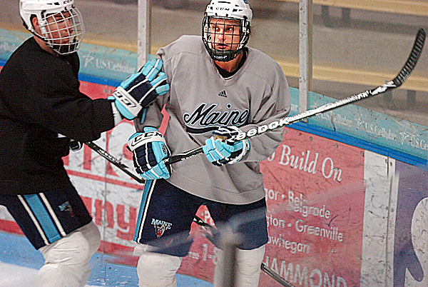 UMaine's Theo Andersson (right) gets pressure in the corner at practice Wednesday, Jan. 6, 2010 at the Alfond Arena in Orono. BANGOR DAILY NEWS PHOTO BY BRIDGET BROWN