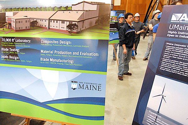 Students and others were on hand at the University of Maine's  Advanced Structures & Composites Center in Orono for Friday's announcement of $12.5 million of federal funding for University of Maine's future Advance Nanocomposites in Renewable Energy Laboratory. The new structure is the addition shown attached to the AEWC in the upper right of the poster shown.   BANGOR DAILY NEWS PHOTO BY JOHN CLARKE RUSS