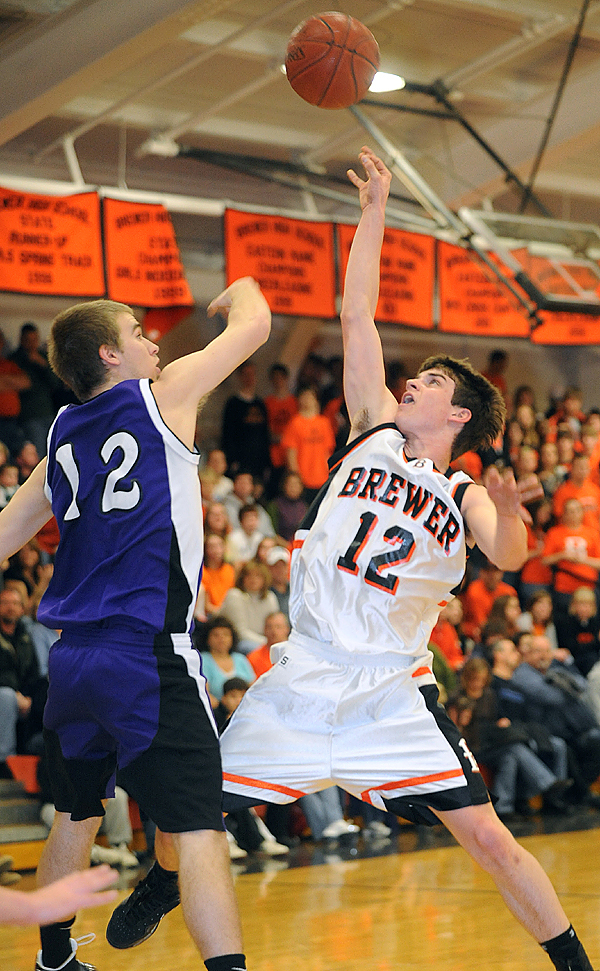 Brewer High School's Ray Bessette (right) makes a shot over Hampden Academy's Bradford Hersey during the first half of the game in Brewer Saturday evening. BANGOR DAILY NEWS PHOTO BY GABOR DEGRE
