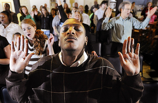 William Dairyko of Bangor and other congregants lift up their hands to the Lord during Destiny Worship Center's Sunday service held in Next Generation Theatre in Brewer November 22,2009. Since starting the congregation in March 2009, Pastor Brian Hurst has seen the congregation steadily grow. BANGOR DAILY NEWS PHOTO BY JOHN CLARKE RUSS