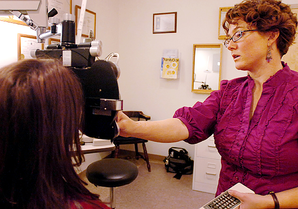 Dr. Kimberly Allen (right), an optometrist with Penobscot Eye Care in Brewer, examines Lori Spellman of Levant on Friday, Jan. 8, 2010. Allen is one of the only eye doctors in the area using Ortho-K lenses which are worn overnight to reshape the eye's cornea. BANGOR DAILY NEWS PHOTO BY BRIDGET BROWN