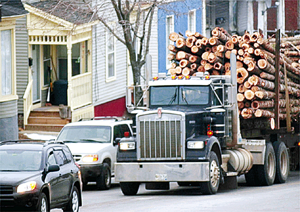 (BANGOR DAILY NEWS PHOTO BY BRIDGET BROWN)  CAPTION  A log truck waits at a red light on Union Street in Bangor near the intersection with Hammond Street on Friday, Feb. 1, 2008. The state Legislature is currently considering a bill which would increase weight limits from 100,000 pounds to 105,000 pounds for six-axle trucks until April 1 to ease the strain of high diseal-fuel prices. (Bangor Daily News/Bridget Brown)