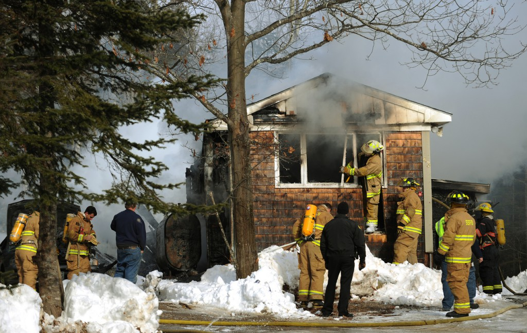 Firefighters from Stocton Springs, Prospect and Searsport inspect a mobile home at 43 Harris Road in Stockton Springs on Monday, Jan. 11, 2010. No one was home at the time the fire was reported. The State Fire Marshal's office has been called in to investigate further. (Bangor Daily News/Kevin Bennett)