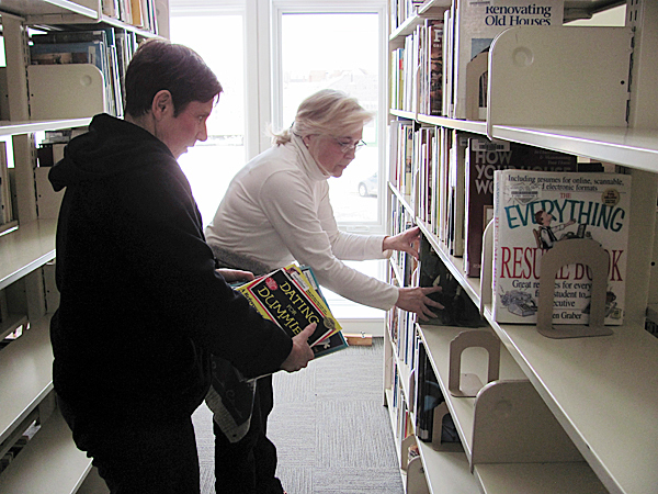 Sue Leibowitz (foreground) and Jeanne Boisvert, members of Friends of Pittsfield Public Library, work to re-shelve thousands of books Monday following a major expansion and renovation of the library. BANGOR DAILY NEWS PHOTO BY CHRISTOPHER COUSINS