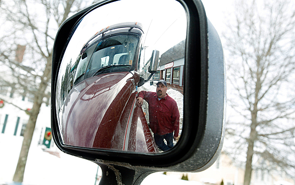 Joe Cormier, a truck driver for H.O. Bouchard Inc., is seen in his rear-view mirror, while taking a break as he passes through his former trucking route on Rt. 1 in Freeport, Maine, on Monday, Jan. 4, 2010. Heavy trucks used to creep through town,  because they weren't allowed on Interstate 295 a quarter-mile away. But most of the trucks have disappeared,  with the passage of a new law that allows heavier trucks, weighing 100,000 pounds ,to use interstate highways in Maine.Those 50-ton behemoths no longer have to dodge tourists and shoppers crossing busy Freeport's Main Street since President Barack Obama signed a measure Dec. 16 allowing the heavy trucks on Maine's interstates. A similar one-year pilot program was approved in Vermont, as well.  (AP Photo/Pat Wellenbach) .(AP Photo/Pat Wellenbach)