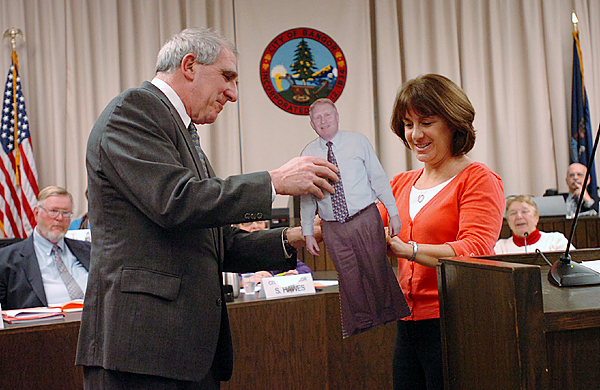 Bangor City Council Chairman Richard Stone presents Bonnie Farrar with a cardboard likeness of her husband, Robert Farrar, at Monday's meeting Jan. 11, 2010, during which he was appointed as the Interim City Manager. (Bangor Daily News/Bridget Brown)