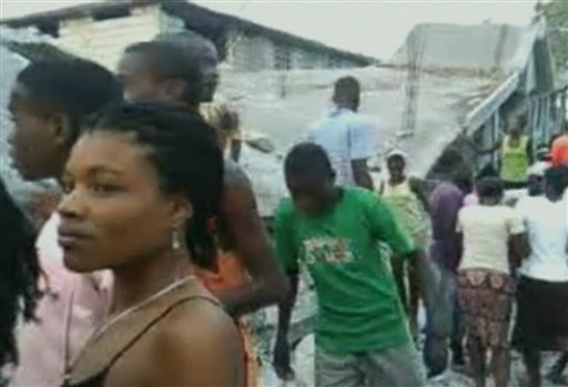 People stand next to the rubble of a badly damaged structure in the southern Haitian town of Les Cayes 122 miles, 196 kms west of the capital Port-au-Princes in this image taken from amateur video Wednesday Jan. 13, 2010.  Haitians piled bodies along the devastated streets of their capital Wednesday after the strongest earthquake to hit the poor Caribbean nation in more than 200 years crushed thousands of structures, from schools and shacks to the National Palace and the U.N. peacekeeping headquarters. Untold numbers were still trapped. (AP Photo/Global Orphan Project, via APTN)  **  TV OUT  **