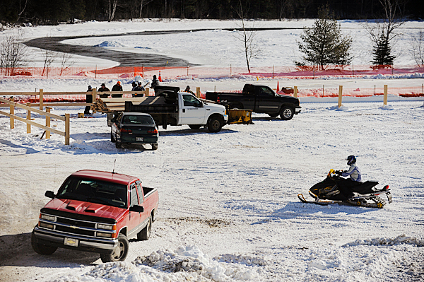 A member of the East Branch Sno-Rovers Club rides his snowmobile past the construction site of the club's soon-to-be-completed 2400-foot-long ice snowmobile racing track near the snowmobile clubhouse in Medway. Photographed January 9, 2010. BANGOR DAILY NEWS PHOTO BY JOHN CLARKE RUSS