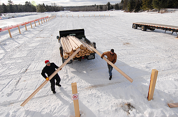 Sterling Thompson, left, and Wesley Perry, members of the East Branch Sno-Rovers Club, unload lumber for new spectator fencing next to the  soon-to-be-completed 2400-foot-long ice snowmobile racing track near the clubhouse in Medway. Photographed January 9, 2010. BANGOR DAILY NEWS PHOTO BY JOHN CLARKE RUSS