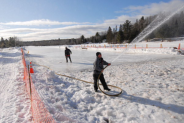 Taking advantage of Saturday morning's cold temperature, Willard Perry of Medway, a member of the East Branch Sno-Rovers Club, sprays water on the soon-to-be-completed 2400-foot-long ice snowmobile racing track next to the snowmobile clubhouse in Medway. Photographed January 9, 2010. BANGOR DAILY NEWS PHOTO BY JOHN CLARKE RUSS