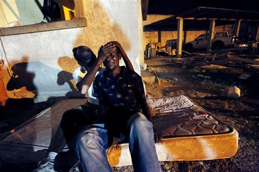 Gunsly Milsoit, left, comforts his brother-in-law Leo Pierre after Leo's wife and Gunsly's sister, Milsoit Kelly, who was three months pregnant, died in a four story building collapse from the 7.0-magnitude earthquake in Port-au-Prince, Haiti, Wednesday, Jan. 13, 2010. (AP Photo/Gerald Herbert)