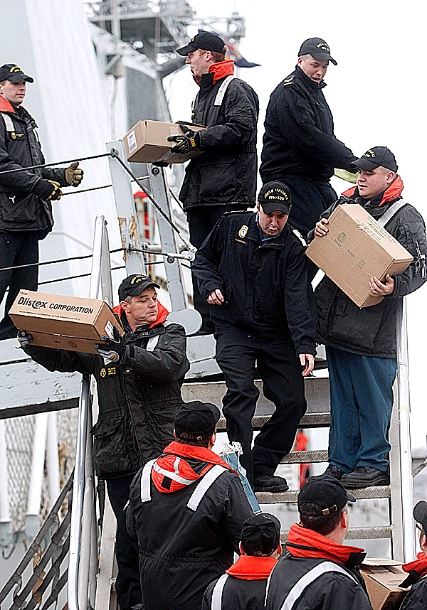 Military personal from HMCS Halifax take on supplies as other crew members try and exit the ship on Thursday, January 14, 2010 in Halifax, Nova Scotia. HMCS Halifax and Athabaskan have left Halifax for Haiti loaded with provisions to help in the international earthquake relief effort. THE CANADIAN PRESS/Mike Dembeck.