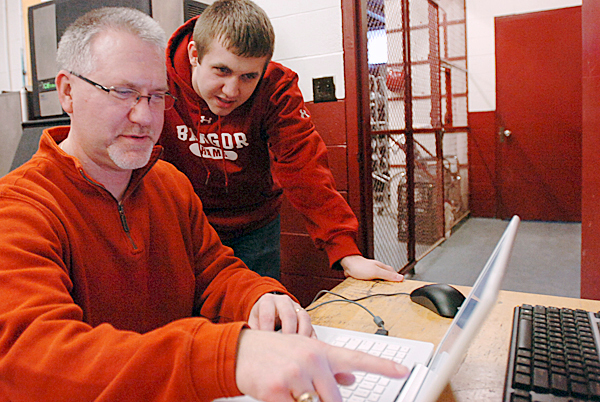 "Bangor High School athletic trainer John Ryan (left) goes over the ImPACT or Immediate Post-Concussion Assessment and Cognitive Testing, exam with his son Nick Ryan, 17, a senior student-athlete on the football team at Bangor High School on Wednesday, Jan. 13, 2010. According to John Ryan, the test, which he started using in the fall of this school year, is to ""better manage athletes who [we] suspect have a concussion."" Ryan also said that 30 Maine schools are currently using the program and that he and a group of other trainers and medical professionals are trying to get it into every high school in the state. (Bangor Daily News/Bridget Brown)"