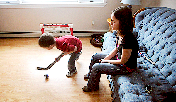 Jenny St.Louis, 24, of Old Town watches her older son Dominique, 6, play hockey in the living room after school Friday.  Jenny has not been able to find a job for nearly a year and her husband Nicholas St.Louis a heavy equipment operator have been out of work for about 15 months.  Jenny went back to school to become a certified nurse assistant and phlebotomist but have not been able to find work after applying for about 20 jobs since December. BANGOR DAILY NEWS PHOTO BY GABOR DEGRE