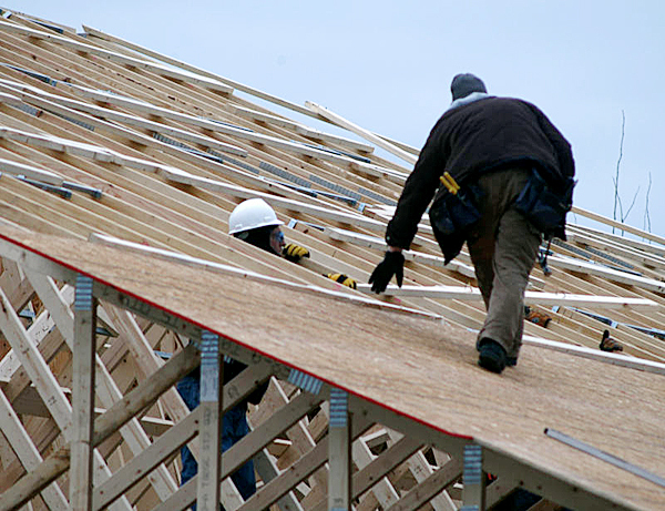 Workers atop the new Lincoln News building at 78 West Broadway place roof panels and planks on Friday.   BANGOR DAILY NEWS PHOTO BY NICK SAMBIDES JR.
