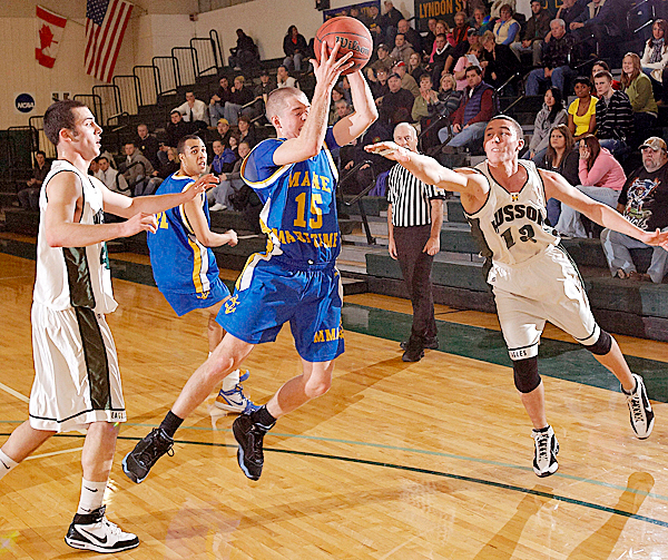 MMA's Ben Russell, (15), grabs a loose ball from Husson's Dwayne Mitchell, (4), and Eric Modica, (13), in the first half of their game in Bangor, Friday, Jan. 15, 2010.