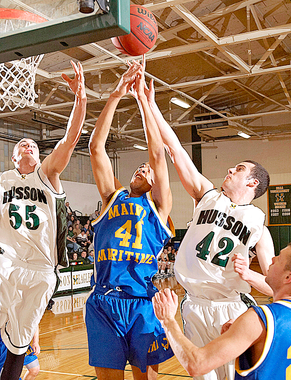 MMA's Shawn Dostie, (41), tries to get a rebound from Husson's Brooks, Spaulding, (55), and John Klages, (42), in the first half of their game in Bangor, Friday, Jan. 15, 2010.   BANGOR DAILY NEWS PHOTO BY MICHAEL C. YORK