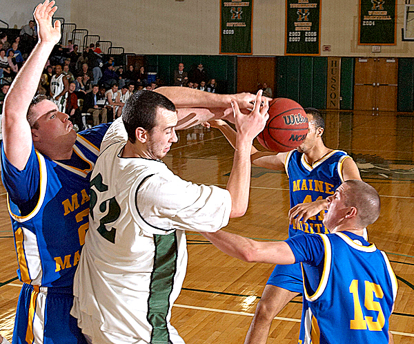 MMA's Jarred Sternbergh, (24), Ben Russell, (15), and Shawn Dostie, (41), corral Husson's Marc Zaharchuk, (52), for the loose ball in the first half of their game in Bangor, Friday, Jan. 15, 2010.   BANGOR DAILY NEWS PHOTO BY MICHAEL C. YORK