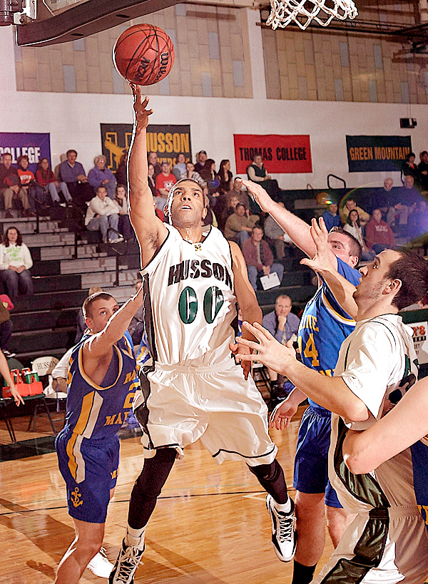 Husson's Joshua Jones, (00), drives to the hoop past MMA's Sam Bell, (22), and Travis Shaw, (24), in the first half of their game in Bangor, Friday, Jan. 15, 2010.