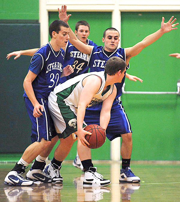 Schecnk's Eric Theriault finds himself surrounded by Sterns defensemen, Brandon McLaughlin, left, Brandon Bouchard, center, and Josh MacDonald, right, during first quarter action on Friday, Jan. 15, 2010 at Schecnk.   BANGOR DAILY NEWS PHOTO BY KEVIN BENNETT