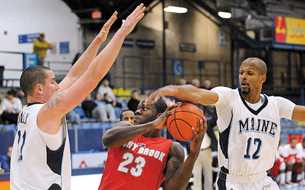 The University of Maine's Sean McNally (left) and Junior Bernal (right) block Stony Brook's Dallis Joner during the first half of the game in Orono Saturday afternoon.  The Black Bears won the game 67-61. (Bangor Daily News/Gabor Degre)
