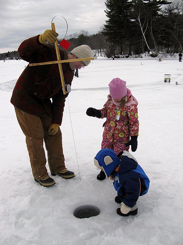 Victor Ahlefeld, 2, of Liberty, and his sister Greta, 5, peer Sunday morning into an ice fishing hole at Lake St. George State Park as their father, Vic Ahlefeld, looks on. The family took part in a youth ice fishing derby that was sponsored by the Maine Bureau of Parks and Lands, which is celebrating its 75th anniversary this year. BANGOR DAILY NEWS PHOTO BY ABIGAIL CURTIS