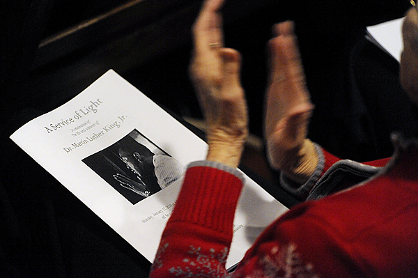 A congregant claps to the music with a church program in her lap showing a photo of the Rev. Dr. Martin Luther King, Jr. during Sunday afternoon's &quot Service of Light&quot in remembrance of Dr. King at All Souls Congregational Church in Bangor. (Bangor Daily News/John Clarke Russ)