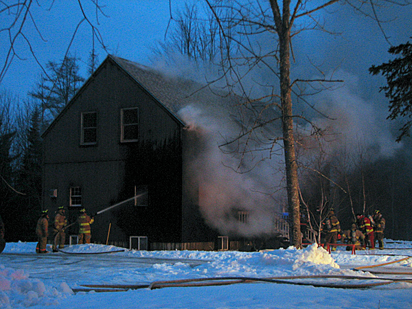 Firefighters battle a fire Sunday night on Point Road in Hancock. Chris Holmes, Hancock's fire chief, said Monday that no one was home at the time of the fire, which may have started in the kitchen area. The house was largely destroyed. BANGOR DAILY NEWS PHOTO BY BILL TROTTER