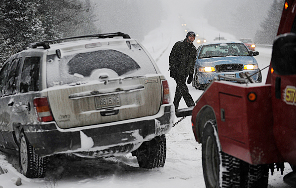 Mike Cole of Exeter watches Doug Sinclair (not pictured) of Hermon-based Sinclair Towing as Sinclair pulls his wife's Jeep Cherokee from an embankment off I-95 northbound, just south of Route 69 in Newburgh after Cole's wife, Christina Cole, lost control of the S.U.V. on her way to Orono during Monday morning's snowy conditions. Mike Cole drove from their home to pick her up. No one was injured. BANGOR DAILY NEWS PHOTO BY JOHN CLARKE RUSS